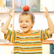 Adorable boy balancing a red apple — Stock Photo #6409200