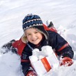 Happy boy in the snow with snowballs in a box — Stock Photo