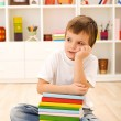 Boy with lots of books thinking — Stock fotografie