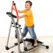 Smiling boy on elliptical trainer in the gym — Stock Photo #6409361