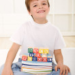 Happy kid with school books sitting on the floor — Stock Photo