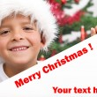 Happy boy with christmas hat and white banner — Stock Photo #6409377