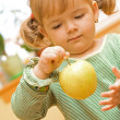 Girl playing with apple — Stock Photo #6409554