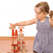 Little girl playing with wooden blocks — Stock Photo #6409561