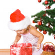 Little girl with present and christmas tree — Stock Photo