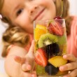 Happy healthy little girl with fruit salad — Stock Photo