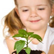 Happy little girl holding a new plant with soil — Stock Photo #6409696
