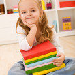 Little girl with a stack of books — Stock Photo