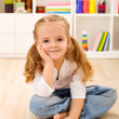 Happy little girl sitting in her room at home — Stock Photo