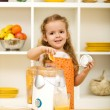 Little girl making fresh fruit juice — Stock Photo #6409800