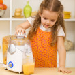 Little girl making fresh fruit juice - Stock Photo