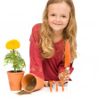 Little girl with gardening tools and potted flower — Stock Photo #6409825
