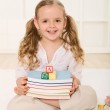 Little girl with books and alphabet wooden blocks — Stock Photo