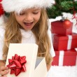 Excited little girl opening christmas present - Stockfoto