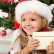 Stock Photo: Happy little girl with christmas present