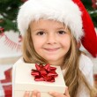 Little girl with present and christmas hat — Stock Photo