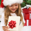 Little girl opening christmas present — Stockfoto