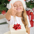 Extremely happy litte girl with christmas present - Stock Photo