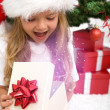 Excited little girl opening christmas present - 图库照片