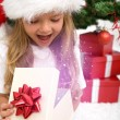 Excited little girl opening christmas present - Foto Stock