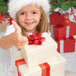 Happy little girl with lots of christmas presents - Stock Photo