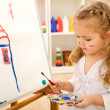 Little artist girl painting on large paper canvas — Stock Photo #6409989