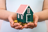 House on a pile of money in woman hands — Stock Photo