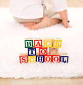 Child turning away from toy blocks - back to school theme — Stock Photo