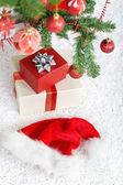 Presents and santa hat under the christmas tree — Foto de Stock