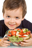 Little smiling boy with a bowl of sliced fruits — Stock Photo