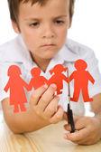 Sad kid cutting his paper family — Stock Photo