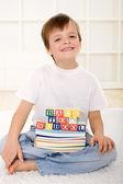 Katta oturan okul kitapları ile mutlu bir çocukluk — Stok fotoğraf