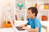 Pojke spelar eller arbetar på bärbar dator — Stockfoto