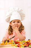 Little girl chief making fresh fruit salad — Stock Photo
