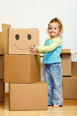 Little girl with lots of cardboard boxes grimacing — Stock Photo