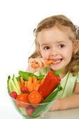 Little girl tasting and chomping a carrot — Stock Photo