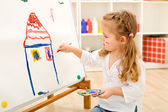 Little artist girl with her masterpiece — Stock Photo