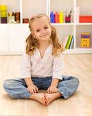 Happy healthy little girl sitting on the floor — Stock Photo