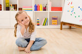 Happy little girl in her room sitting — Stock Photo