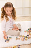 Little girl playing with wooden blocks — Stock Photo