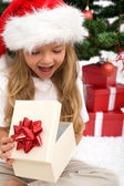 Excited little girl opening christmas present — Stok fotoğraf