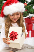 Little girl opening christmas present — Stock Photo