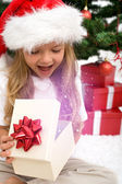 Excited little girl opening christmas present — Zdjęcie stockowe