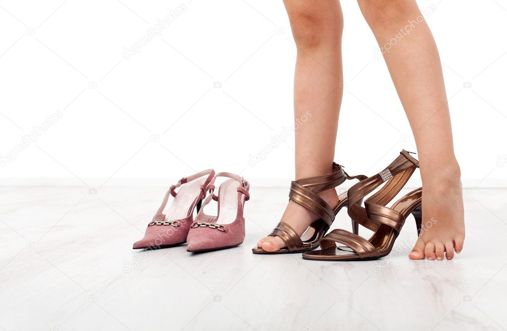 Little girl feet trying large shoes with high heels — Stock Photo #6405470