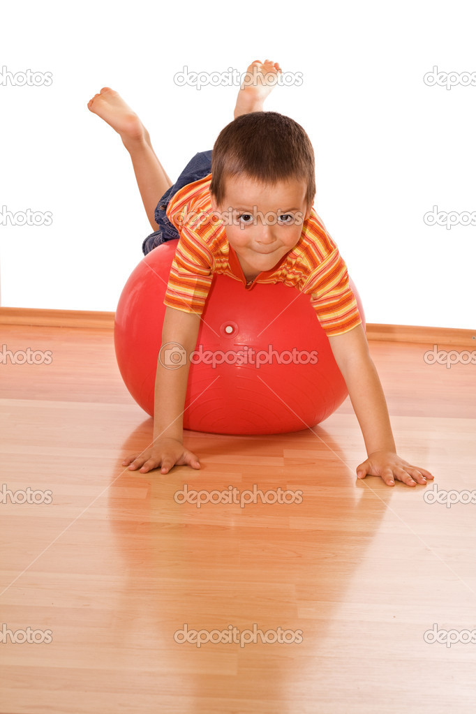 Little boy playing with a huge red gymnastic ball — Stock Photo #6409204