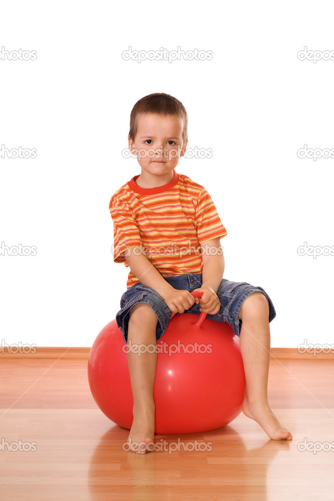 Serious little boy sitting on a gymnastic rubber ball - isolated — Stock Photo #6409206