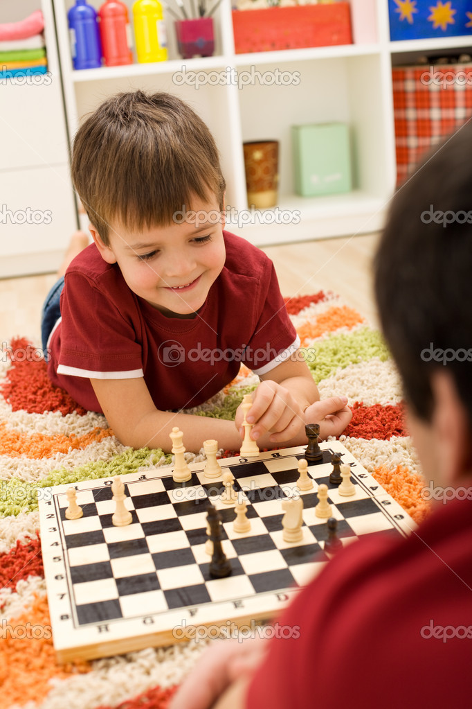 Learning the rules of chess - kid with father playing on the floor — Stock Photo #6409330