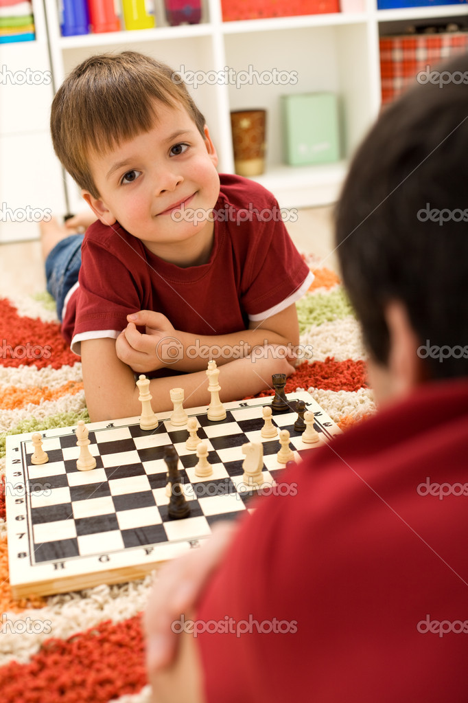 Little boy laying on the floor playing chess — Stock Photo #6409335