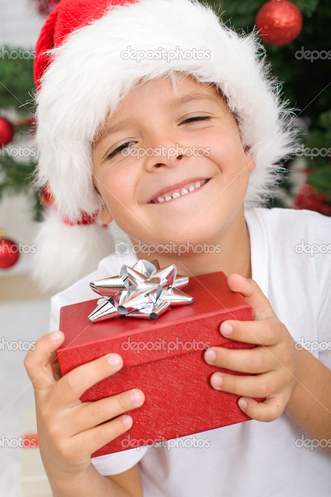 Happy boy smiling, holding christmas present - closeup — Stock Photo #6409382