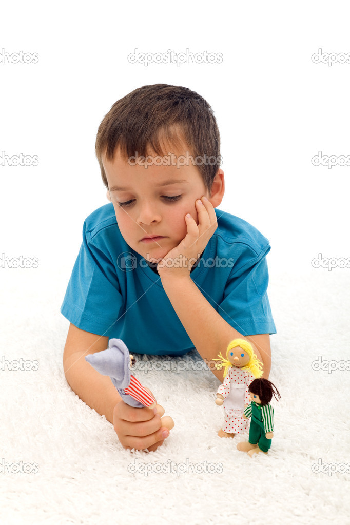 Divorce effect on kids  concept with thoughtful boy playing with puppets on the floor - isolated — Stock Photo #6409397
